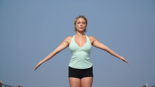 Thumbnail for A young attractive woman doing yoga on the pier.