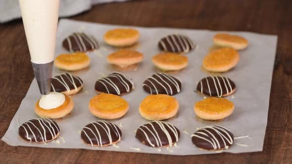 Thumbnail for Making Homemade Cookies with Apricot Jam and Whipping Cream. Hand with Confectionery Bag Squeezing