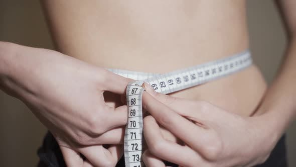 Thumbnail for Attractive Woman with Naked Stomach Measuring Her Waist