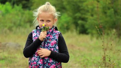 A portrait of a cute little girl. Beautiful Little girl enjoys the smell of flowers in the meadow