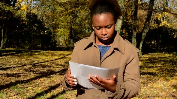Thumbnail for Young Beautiful African Serious Girl Stands in Woods, Holds Some Papers and Reads