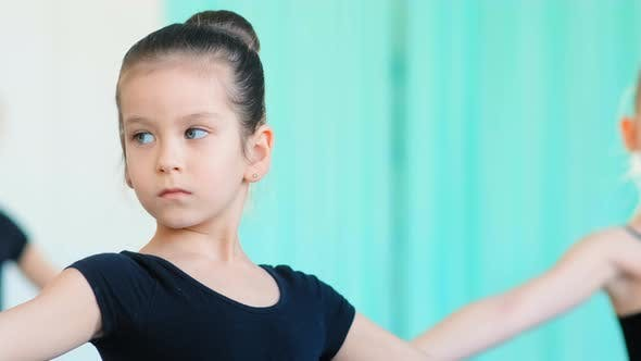 Thumbnail for Concentrated Little Girl with Blue Eyes Practices Ballet