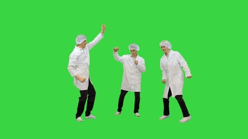 Three Male Doctors in White Robes and Protective Caps Doing Funny Celebration Dance on a Green