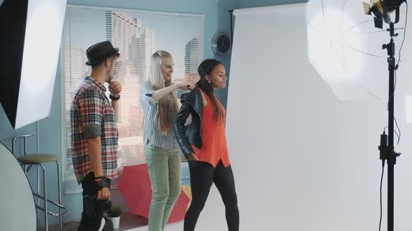 Behind the Scenes on Photo Shoot Assistant Helping Mixedrace Model to Wear Jacket During Photo