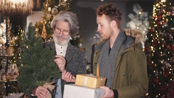Thumbnail for Senior und junger Mann blickt auf Weihnachtsbaum-Shopping im Weihnachtsdekorationsgeschäft