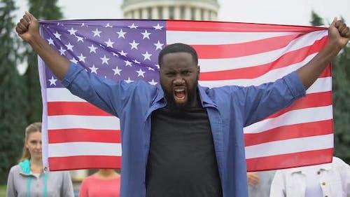Irritated Black Man Raising American Flag, Anti-Racist Rally, US Migrant Crisis