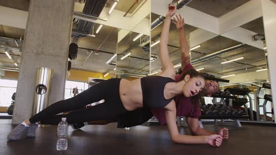 Thumbnail for Fit healthy happy Black and Hispanic couple doing core exercises in gym together
