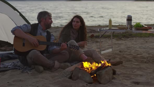 Thumbnail for Man Playing Guitar and Woman Eating Sausage by Campfire on Beach