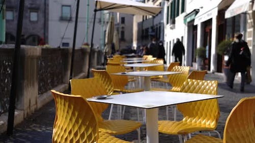 White Open Cafe Tables Stand Among Yellow Chairs on Sidewalk