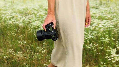 Unrecognizable woman hold digital camera in her hands on flower field landscape