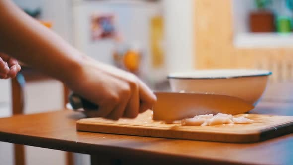 Thumbnail for Woman Hands with a Knife Cutting Meat on a Wooden Cutting Board in the Home Kitchen. Slow Motion