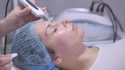 Cosmetologist Using Ultrasonic Scrubber on Clients Face