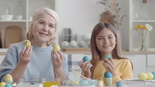 Thumbnail for Happy Grandma and Granddaughter Holding Easter Eggs and Posing for Camera