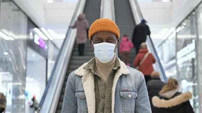 African American Guy Puts on Blue Disposable Face Mask