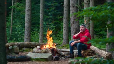 Bearded Male Tourist Near Campfire in the Forest