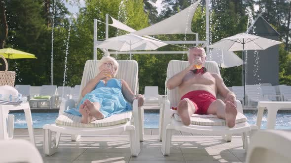 Thumbnail for Mature Couple Lying on Sunbeds Near the Pool Drinking Juice
