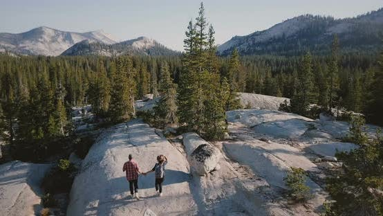 Thumbnail for Drone Camera Follows Young Happy Couple Run and Hike Together on Amazing White Rock Towards Epic