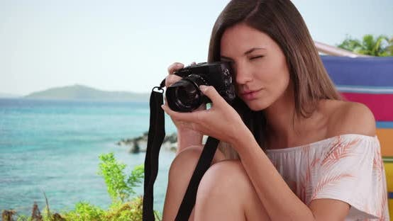 Thumbnail for Young female photographer relaxing near ocean taking picture of something