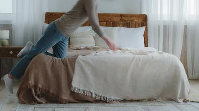 Exhausted Bored Young Woman Falling Down on Bed in Bedroom