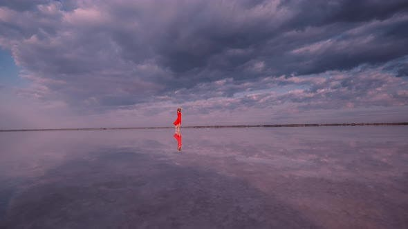 Thumbnail for Tourist Girl Is Walking Along a Salt Lake in Which Clouds Are Reflected.