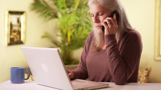 Thumbnail for Modern middle aged woman using cell phone and laptop
