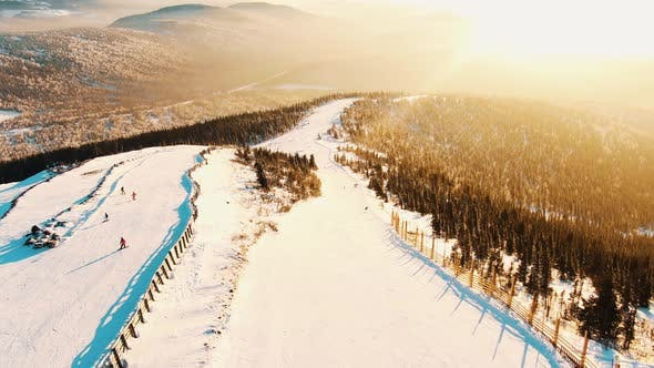 Aerial View of the Slopes and Slopes of the Ski Resort at Sunset Skiers and Snowboarders Roll Along