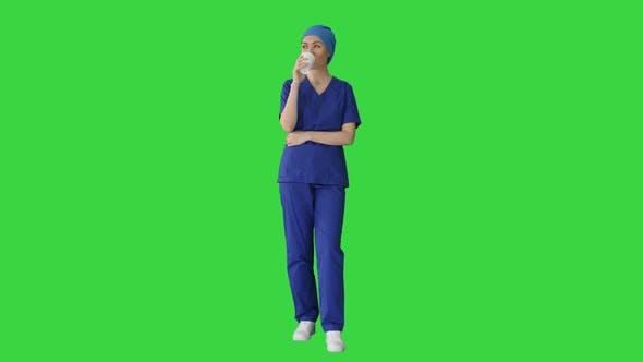 Smiling Female Doctor or Nurse in Blue Uniform Having a Coffee Break on a Green Screen Chroma Key