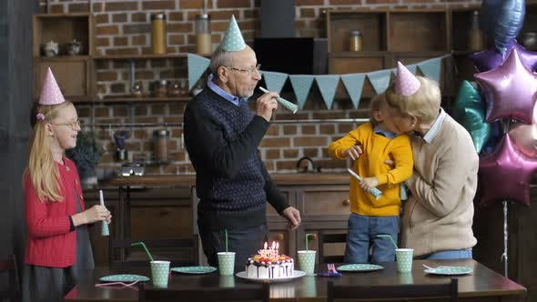 Thumbnail for Happy Family Blowing Horns at Boy's Birthday Party