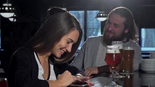 Thumbnail for Beautiful Happy Woman Using Her Smartphone, Drinking Beer with Friends