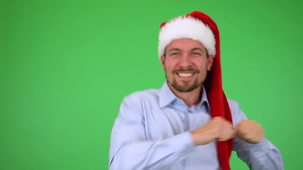 Thumbnail for A Young Handsome Man in a Christmas Hat Dances and Smiles at the Camera - Green Screen Studio