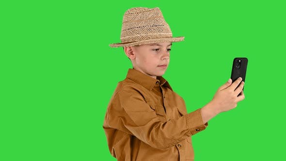 Kleiner Junge mit Strohhut, der sich umschVideo, während er auf einem grünen Bildschirm telefoniert