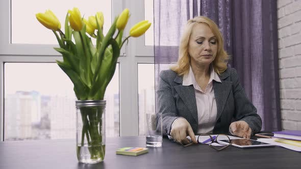 Thumbnail for Senior Woman Taking Pills From Headache at Office