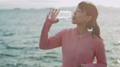 Woman runner drinking water while standing seaside.