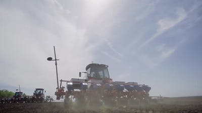 Tractor with Seeder Works in the Field Back View