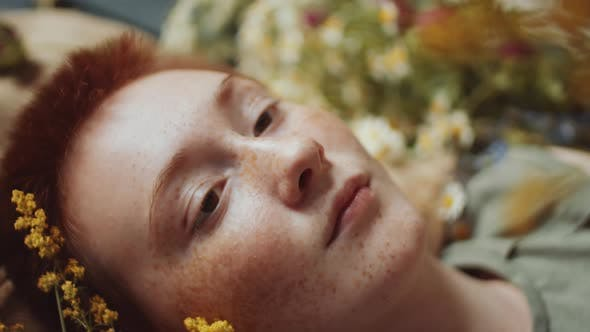 Dreamy Woman with Ginger Hair Holding Yellow Wildflower