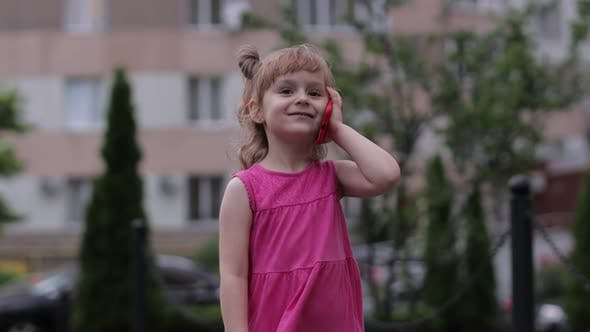 Thumbnail for Child Girl Talking By Smartphone Outdoors. Kid in Pink Dress Talking By Mobile Phone on City Street