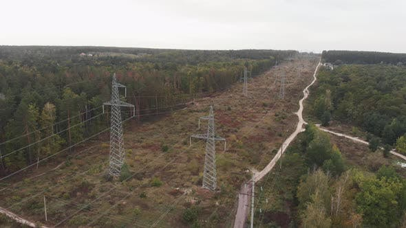 High voltage electric tower in forest. Transmission power lines and electrical equipment