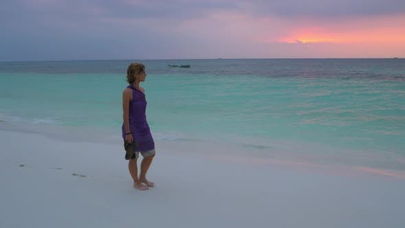 Slow motion: woman on white sand beach turquoise water tropical coastline