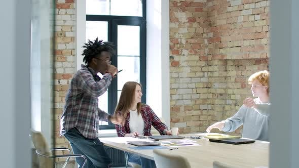 Thumbnail for Wide Shot, Business Meeting of Cheerful Millennial Multiethnic Colleagues in Sunny Office. Positive