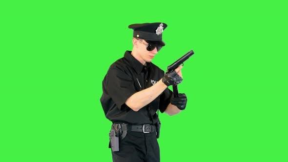 Policeman Walks Doing Some Exercices with His Gun on a Green Screen Chroma Key