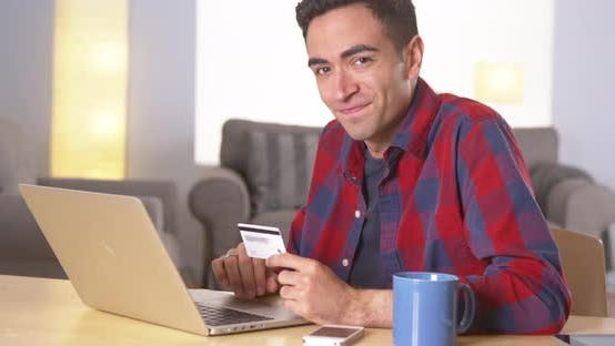 Thumbnail for Hispanic man smiling with credit card