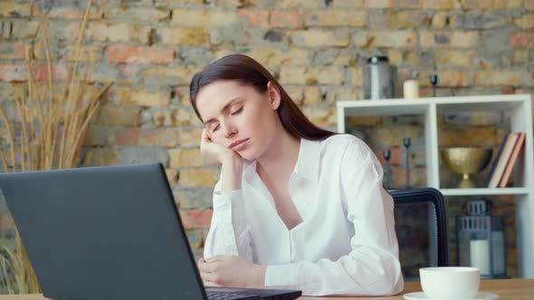 Tired Overworked Businesswoman Sitting at Her Desk in Office Falling Asleep