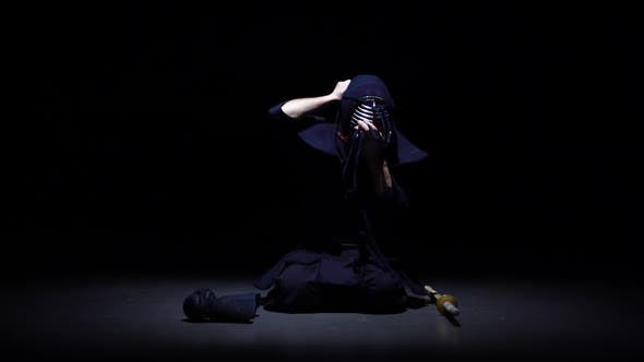 Cover Image for Kendo Warrior Is Putting on Helmet and Lacing It. Slow Motion