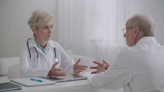 Two Doctors Are Talking in Clinical Office, Consulting with Each Other and Advising, Consilium of