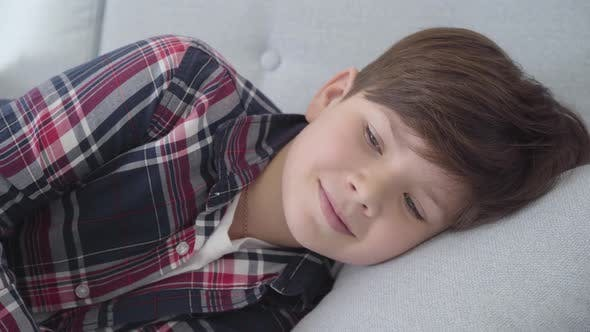 Thumbnail for Close-up Portrait of Cute Caucasian Boy with Brown Hair and Grey Eyes Lying on Soft Pillow. Smiling