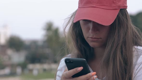 Girl with Long Dark Hair in Red Cap Surfs Internet in Phone