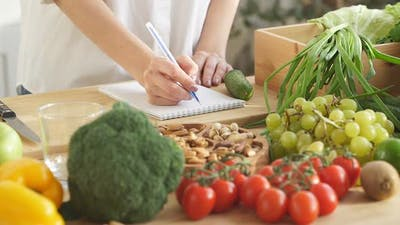 Closeup the Nutritionist Makes Notes in His Notebook About Proper Nutrition There are a Lot of