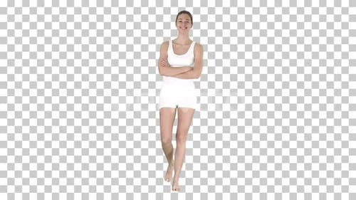 Smiling sports woman walking with arms folded and looking