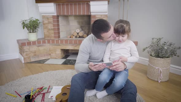 Thumbnail for Portrait of Cute Caucasian Little Girl Sitting with Father and Watching Cartoons on Smartphone