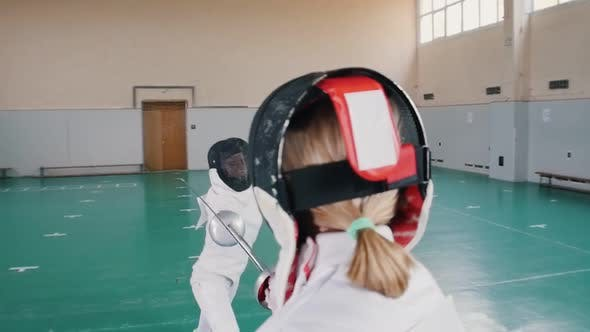 Thumbnail for Two Young Women in White Protective Suits Having a Fencing Training - One Woman Attack and Another